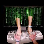 two hands holding each other, one reaching from the matrix of a computer, across a computer keyboard