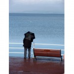 Man with umbrella looks out over Morecambe Bay.